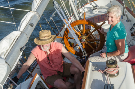 ketch: A happy senior couple enjoys time together sailing on a lake on a fine summer day.