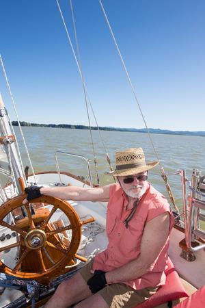 A senior man at the helm of sailboat navigates on Fern Ridge Reservoir near Eugene, Oregon. 免版税图像