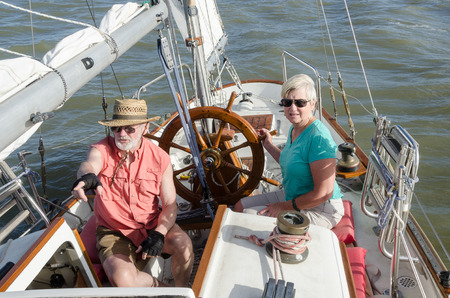 ketch: A senior couple sail on their classic ketch as he points to indications of wind on the water ahead while she steadies the helm. Stock Photo