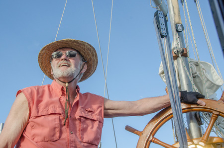 A retired man at the helm of his classic ketch enjoys the summer day under a bright blue sky.