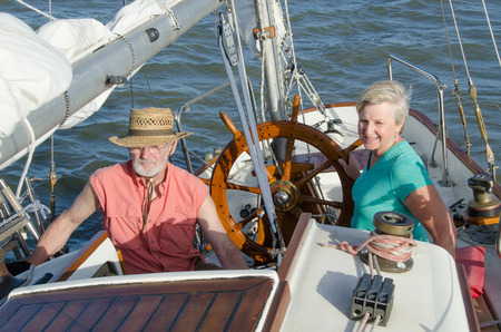 A happy senior couple enjoys time together sailing on a lake on a fine summer day.
