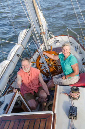 ketch: Portrait of a happy retired couple on their classic ketch as they sail into the hazy late afternoon sun.