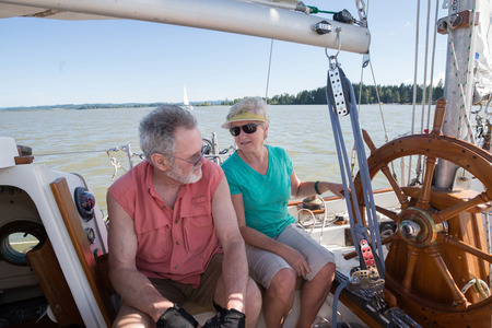 A retired couple on their sailboat converse as they sail on an Oregon lake. 免版税图像