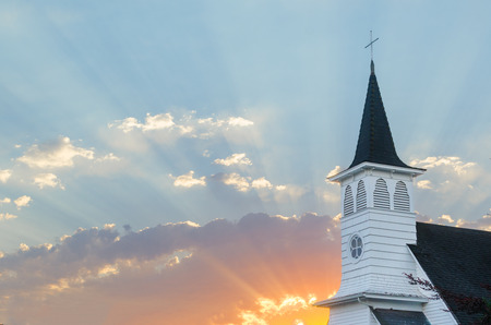 Golden rays of sun burst through the clouds at sunrise with an old Christian church steeple in the far right.