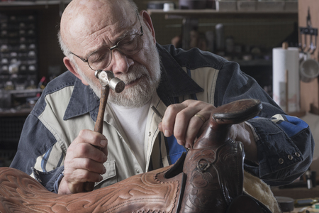 An old saddle repair artist close up with dramatic lighting in his workshop. 免版税图像
