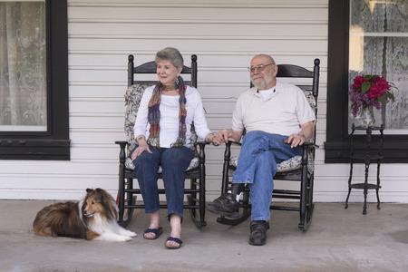 Een bejaarde echtpaar in hun jaren tachtig kijken naar de wereld vanuit hun veranda met hun sheltie hond aan hun zijde. Stockfoto