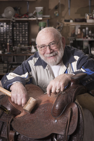 eighties: Portrait of a smilling, happy leather craftsman in his eighties.