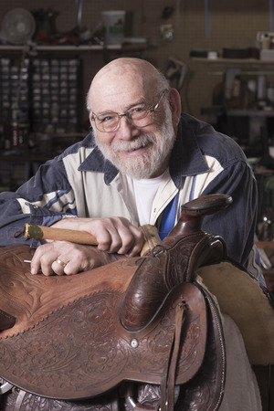A smilling, happy leather craftsman in his eighties in a portrait with dramatic lighting.