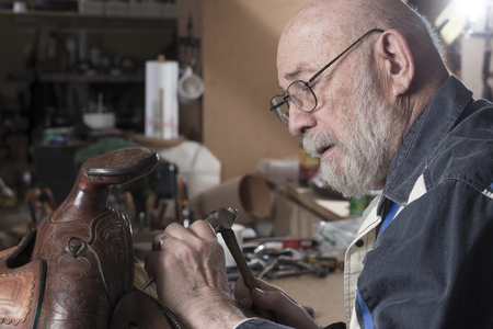 Close up of a saddle being repaired by an experienced craftsman.