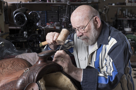 five year old: An eighty five year old saddle repairman places artistic embossing on a saddle. Stock Photo