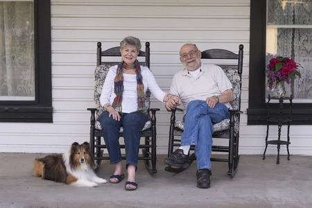 A happy married couple relax on their porch in matching rocking chairs with their Shetland sheepdog by their side.