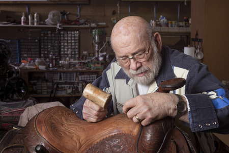 five year old: An eighty five year old saddle repairman working at his craft.