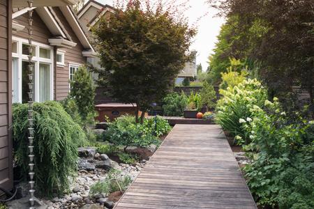 Een lange, smalle houten dek in de achtertuin van een moderne woning.