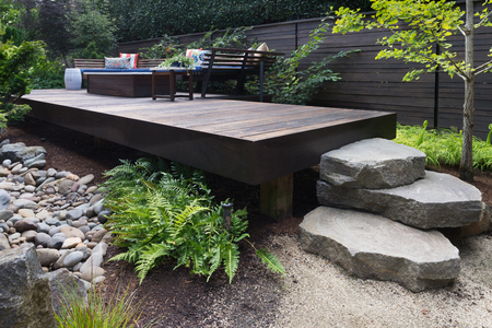 Three massive rocks form steps to a contemporary deck with bench inspired by oriental design. 免版税图像
