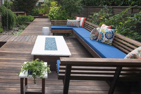 Een eigentijdse outdoor gesprek bank met kussens op een houten dek.