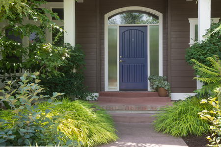 contemporary: A blue door welcomes guests to this contemporary home. Stock Photo