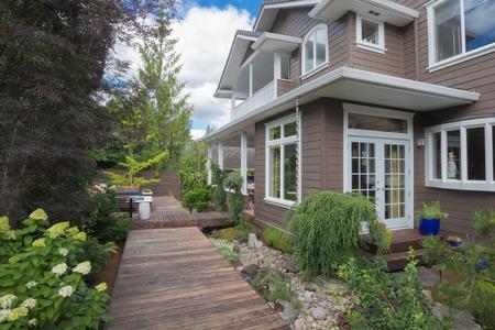 Een smalle dek gaat verleden dubbele deuren in de achtertuin van deze moderne woning.