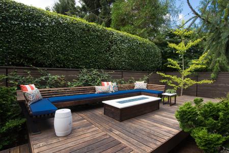 나무 갑판에 베개와 현대 야외 대화 벤치입니다.