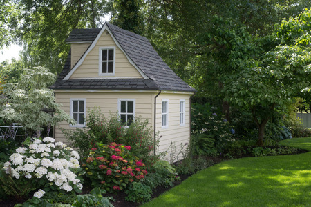 A charming playhouse cottage sits at the edge of a shaded perennial garden. Foto de archivo