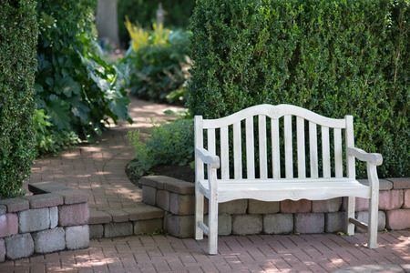 disappears: A whitewashed bench sits near a brick walkway that gradually disappears in soft focus.
