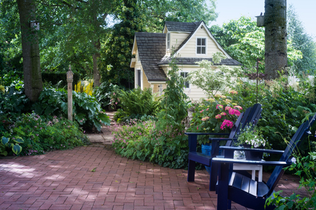 playhouse: A charming playhouse is seen beyond two wooden chairs in a shaded garden patio. Stock Photo