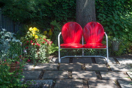 A modern loveseat sits in dappled sun in the back of a garden. Stock Photo