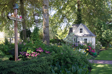 A charming playhouse sits at the edge of a shaded perennial garden.with birdhouses in the foreground.
