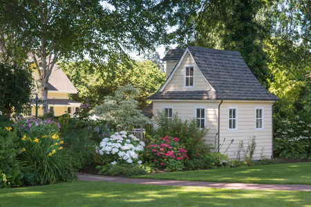 playhouse: A charming playhouse sits in a shaded perennial garden.