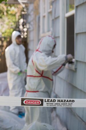2 防護服を着た鉛を取り除くことで画家の家は、古い家からペイントします。 写真素材 - 64035252