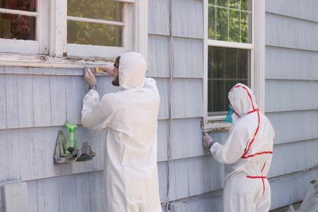 Due pittori di casa in abiti Hazmat rimozione di vernice al piombo da una vecchia casa. Archivio Fotografico - 64035255