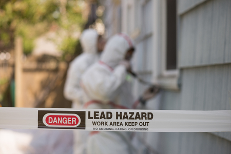 abatement: Two house painters in hazmat suits removing lead paint from an old house.