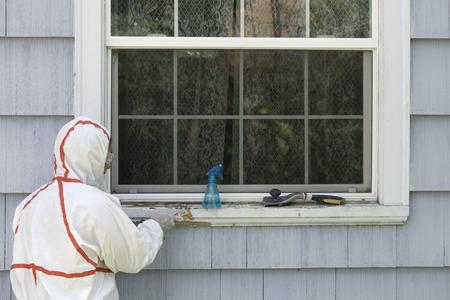 化学防護服の家の画家は、窓枠から危険な鉛ペンキを掻き取る。 写真素材