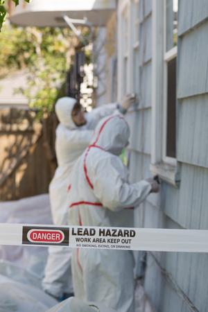 Dos pintores de la casa con trajes especiales eliminación de la pintura con plomo de una casa antigua.