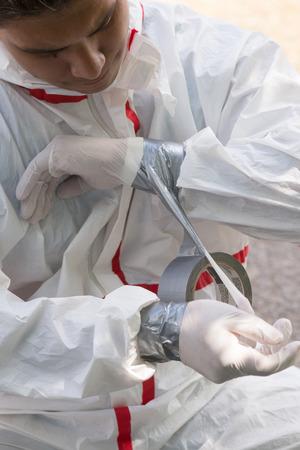 家の画家は、安全に鉛ペンキを削除する準備をして彼の化学防護服の袖を保護します。 写真素材 - 64035258
