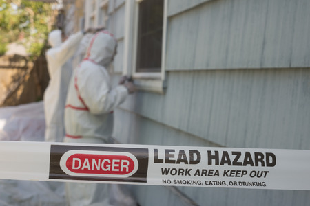 Two house painters in hazmat suits removing lead paint from an old house. Stock Photo - 64035260