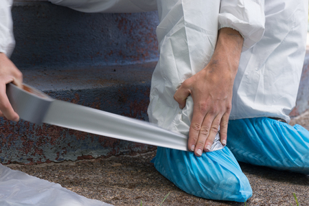 A house painter secures the ankles of his hazmat suit preparing to safely remove lead paint.