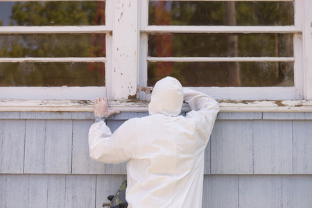 A house painter in a hazmat suit scrapes off dangerous lead paint from a window sill.