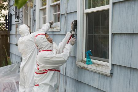 오래 된 집에서 납 페인트를 제거하는 유해 물질의 정장에 두 집 화가. 스톡 콘텐츠