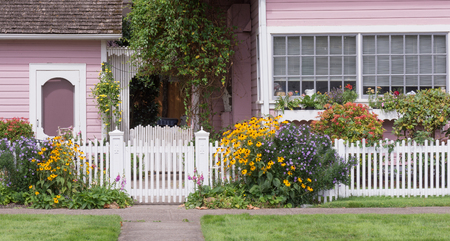 De ingang van een oud Victoriaans huis naast een bijpassend huisje achter een witte houten poort met felgele zwartogige Susans.