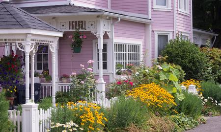 Voorkant van een gerestaureerd Victoriaans huis met een tuin van zomerbloemen