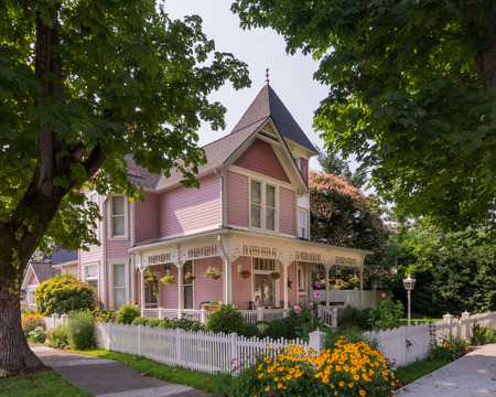 A stately Victorian home with copula is viewed between a pair of ancient maple trees. 写真素材
