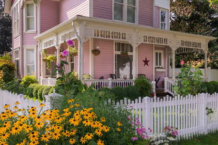 Happy black-eyed Susan flowers explode in front of a classic Victorian home.