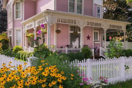 Gelukkige zwarte ogen Susan bloemen exploderen voor een klassiek Victoriaans huis.