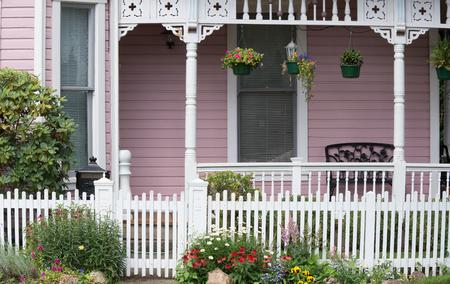 De ingang van een oud Victoriaans huis achter een witte houten poort geflankeerd door madeliefjes, rode zonnehoed, altviolen, astilbes en gele viooltjes. Stockfoto