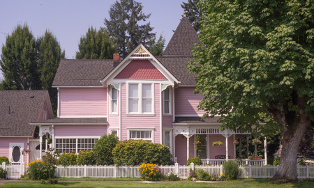 Pink Victoran home beside a stately maple tree. Standard-Bild