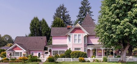 Pink Victorian style home with attached cottage.