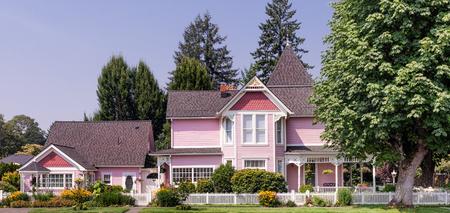 Roze Victoriaanse stijl huis met bijgebouwde cottage.
