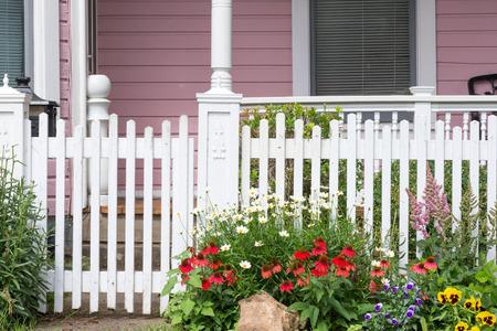 Een wirwar van madeliefjes, rode zonnehoedjes, altviolen, astilbes en gele viooltjes aan de poort naar een roze Victoriaans huis.