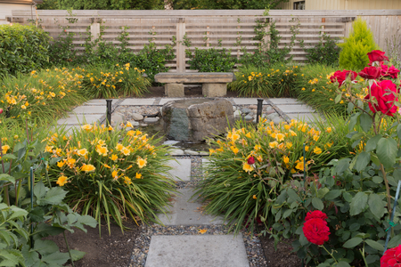 A meditative stone fountain hidden in a backyard garden. Imagens