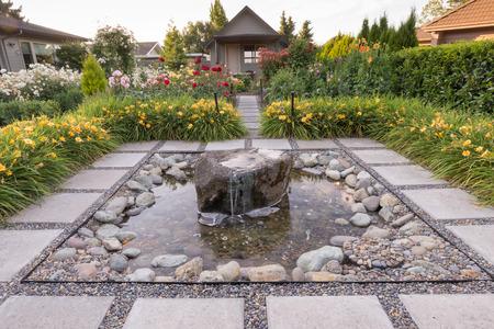 A quiet stone fountain surrounded by day lillies at the end of a backyard garden.
